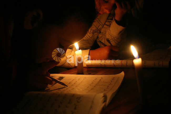 Palestinian children study on the candles light during power outage in Gaza city on February 03, 2013. A Palestinian man died Saturday in northern Gaza after his house caught fire, two days after a family of six, including four children, died in a house fire east of Gaza City, medics said. Photo by Ezz al-Zanoon