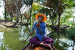 Bangkok, Ladmayom - Thailand, February 25, 2012 -- A man on his boat paddles through the garden canals; people, water transport, infrastructure -- Photo © HorstWagner.eu