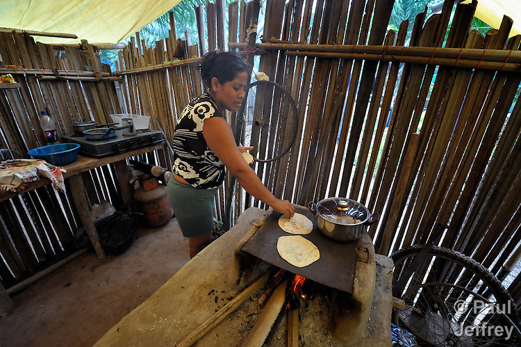 A woman cooks tortillas on her woodstove on the La Lempira Cooperative, near Ceibita, Honduras. La Lempira is an agricultural project which has been seized by armed peasants who claim the land is rightfully theirs under the country's agrarian reform law.