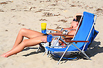 Attractive young woman on vacation naps in folding chair