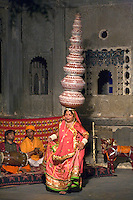 A Rajasthani woman performing a traditional DANCE carrying nine water jugs on her head at the BAGORE KI HAVELI in UDAIPUR - RAJASTHAN, INDIA