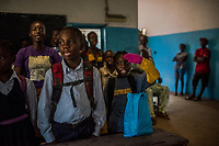 "MONROVIA, LIBERIA - FEBRUARY 16: Second grade student, James Nyema, 9, wearing a pair of pink mittens, salutes as he sings the national anthem of Liberia, during assembly on the first day of school, since Schools closed 6 months ago due to the Ebola outbreak, at the C.D.B. King Elementary School in Monrovia, Liberia. A second-grade boy in the first row sported pink knit mittens that muffled the sound of his clapping when the teachers introduced themselves. As everyone rose to sing Liberia's national anthem, he saluted with his left hand, still sheathed in the mitten.<br /> ""Ebola destroyed and devastated our land,'' Venoria Crayton, the vice principal, told her pupils. ""It brought us sadness, it brought us pain. Some of your neighbors died, right? Some of your neighbor's children died, right? But you are here."" <br /> James' mother had dressed him in trousers and long sleeves, which he usually wore only during the rainy season – not now, the driest and hottest time of the year. The mittens she had bought at a nearby market where they had become available during the height of the epidemic last year. Didn't she worry that her son might overheat? ""I was afraid, but what can I do?'' she said, laughing again.<br /> Daniel Berehulak for The New York Times"