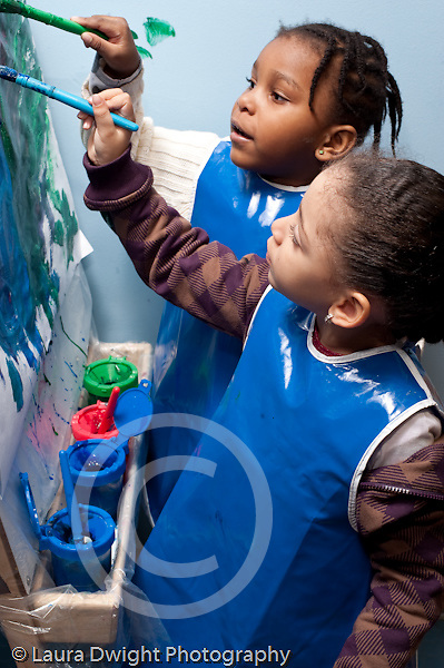 Educaton preschool 4-5 year olds art activity painting at easel two girls at work on the same painting vertical