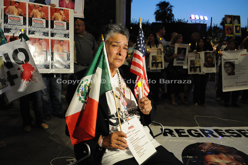 "Phoenix, Arizona - Maria Trujillo Herrera arrived to Phoenix from California as part of the ""Caravan for Peace with Justice and Dignity"" to create awareness about her four missing sons. In this image she sits holding the Mexican and the U.S. flag as she listens to speakers during a rally and vigil held at the Civic Space Park. Two of her four sons - Raul and Jesus Salvador- went missing in August 2008 after going to a business trip to the Mexican state of Guerrero. Her other sons -Luis Armando and Gustavo- disappeared during a trip to the state of Veracruz in September 2010. The ""Caravan for Peace with Justice and Dignity"" stopped in Phoenix on Wednesday, August 15, 2012 as it travels across the United States as a way to create awareness in the United States about the failed drug war in Mexico that has left more than 70,000 dead. The caravan is led by Mexican poet, essayist, novelist, and journalist Javier Sicilia, whose son Juan Francisco Sicilia Ortega son was brutally murdered along with six other students in Morelos, Mexico by members of a drug cartel on March 28, 2011. In response, Sicilia created the Movement for Peace with Justice and Dignity --popularly known as ¡Ya Estamos Hasta la Madre! or We Have Had It!-- calling for an end the drug cartels bloodshed. Photo by Eduardo Barraza © 2012"