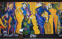 Section of the Berlin Wall depicting the painting Die Tanzenden or the Dancers by Sabine Kunz, damaged by graffiti, part of the East Side Gallery, a 1.3km long section of the Wall on Muhlenstrasse painted in 1990 on its Eastern side by 105 artists from around the world, Berlin, Germany. Picture by Manuel Cohen