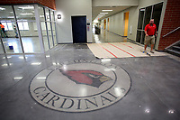 NWA Democrat-Gazette/DAVID GOTTSCHALK   Jon Purifoy, principal at Farmington High School, walks Friday, July 14, 2017, past the school new stained concrete new emblem in the new Farmington High School. Classes will be begin at the new school this August.