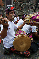 Traditional balinese drummer cheers up the crowd  on day of cremation ceremonies,  September  17th 2011,  family Nyoman Budiana and others, Banjar Pande, Peliatan next to Ubud, Bali, archipelago Indonesia. Cremation ceremonies in Bali guide the spirit of the passed family member from underworld death realms to divine heavenly nature spirit life circle uprise of the death, becoming a divine ancestor to be reborn in the next generation of the family