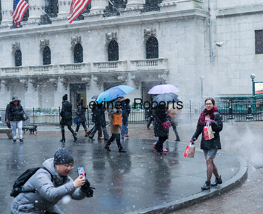Intrepid tourists and downtown workers brave the cold and snow in front of the New York Stock Exchange on Tuesday, January 31, 2017. The snow will wind down by the late afternoon leaving only about an inch in the city. (© Richard B. Levine)