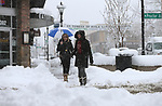 Pat Richer, left, and Judie Rosato walk through more than a foot of snow in downtown Carson City, Nev., on Friday, March 16, 2018. <br />