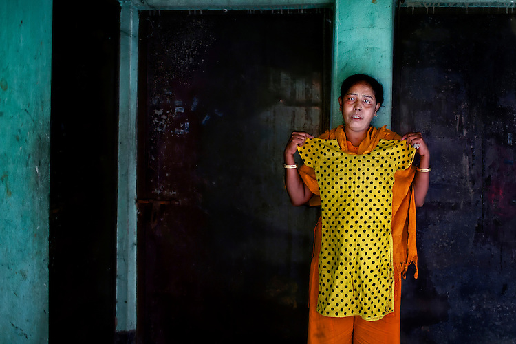 Rokeya Begum weeps as she holds a dress of her teenage daughter Henna Akhtar (17), who died in the fire at Tazreen Fashions, near Ashulia, Bangladesh. Rokeya poses for a portrait in front of the site of Henna's death —the burnt living room next to the factory building.