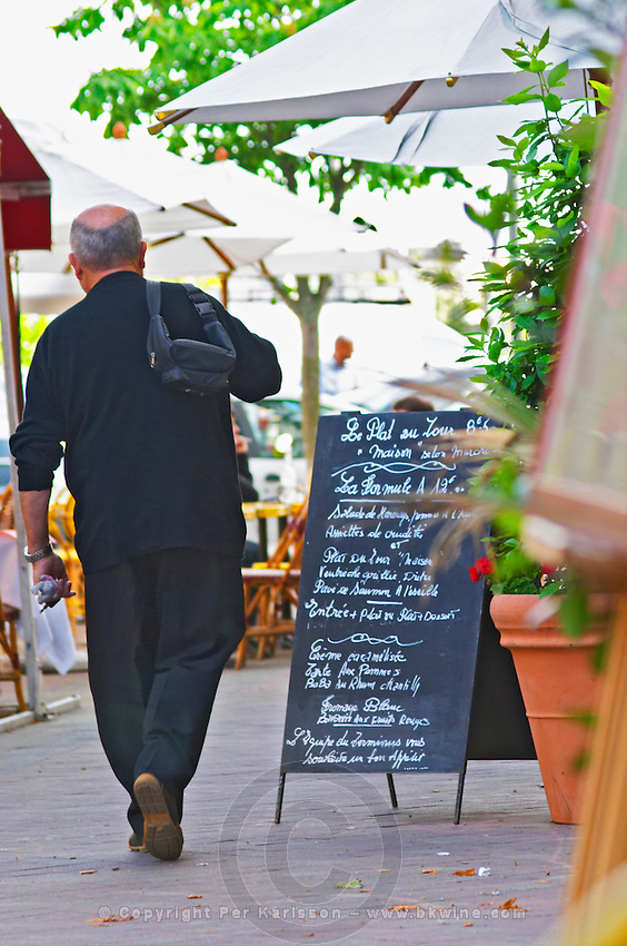 A cafe restaurant with a chalk board chalkboard with today's menu and a man in black walking past. Outside seating terrasse with sun shades parasols  city  Bordeaux Gironde Aquitaine France