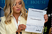 White House Press Secretary Kayleigh McEnany, holds a check, in the amount of United States President Donald J. Trump's annual salary, to be donated to the U.S. Department of Health and Human Services (HHS) during a news conference in the Brady Press Briefing Room of the White House in Washington, D.C., U.S., on Friday, May 22, 2020. Trump ordered states to allow churches to reopen from stay-at-home restrictions imposed to combat the coronavirus outbreak, saying he would override any governor who refuses. <br /> Credit: Andrew Harrer / Pool via CNP