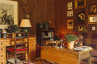 A collection of paintings of dogs and a hunting trophy are displayed on the rough clapboard walls of the living room