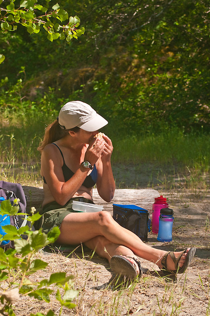 Woman eating a picnic lunch, along the North Fork of the American River, Weimar, California.