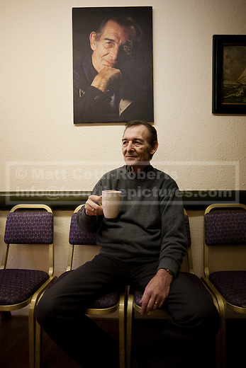 Drinking a cup of tea in a moment of respite, Mike sits below a portrait of himself. Donated years ago by a customer within the photographic industry, it was supposed to be accompanied by an advertising board that never materialised. Mike doesn't have the heart to take it down.