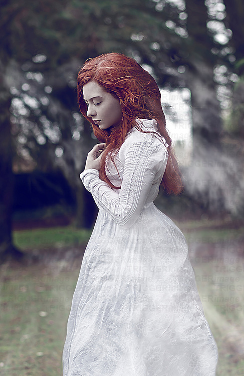 Young woman with long red hair wearing period white dress standing alone outdoors with breeze