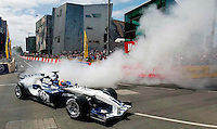 "A Williams F1 car driven by Brazillian test driver Antonio Pizzonia lights up it's rear tyres much to the delight of the lunchtime crowd in Melbourne's CBD during a ""demonstration"""