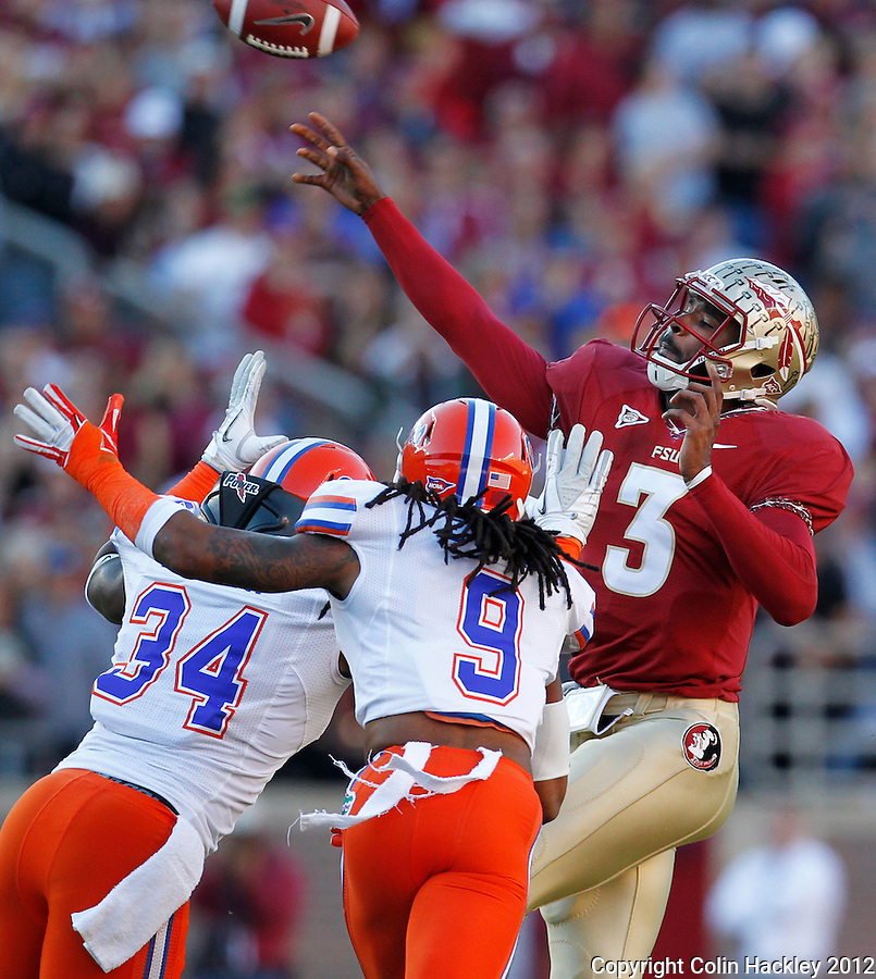 TALLAHASSEE, FL 11/24/12-FSU-UF112412 CH-Under pressure from Florida's Lerentee McCray, left, and Josh Evans, Florida State's EJ Manuel throws his first interception of the game during first half action Saturday at Doak Campbell Stadium in Tallahassee. .COLIN HACKLEY PHOTO