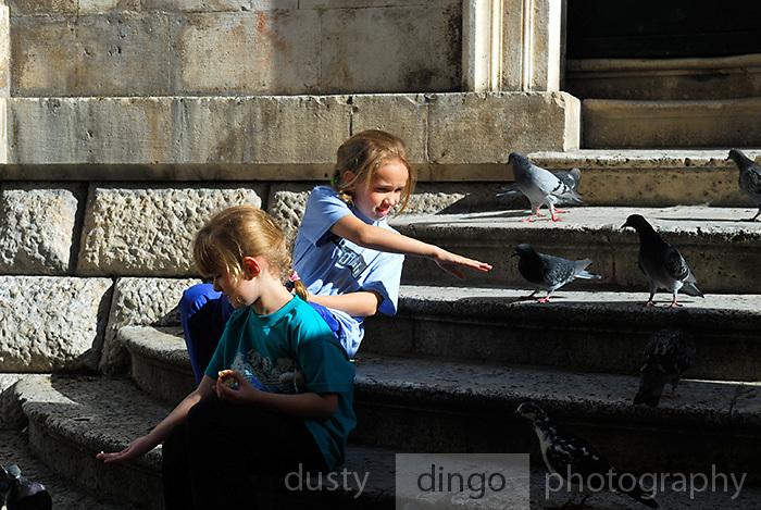 Two children (5 years old, 9 years old) feeding pigeons on Gunduliceva Poljana (Square), Dubrovnik old town, Croatia