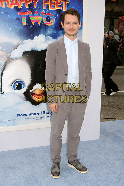 Elijah Wood.The World Premiere of 'Happy Feet Two' held at The Grauman's Chinese Theatre in Hollywood, California, USA..November 13th, 2011.full length suit hands in pockets stubble facial hair grey gray white blue shirt .CAP/ADM/BP.©Byron Purvis/AdMedia/Capital Pictures.