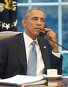 United States President Barack Obama is photographed through an Oval Office window as he speaks on the phone with King Abdallah Abd al Aziz of the Kingdom of Saudi Arabia at White House in Washington, D.C. on Wednesday, September 10, 2014 as he prepares for his speech to the nation this evening. <br /> Credit: Ron Sachs / Pool via CNP