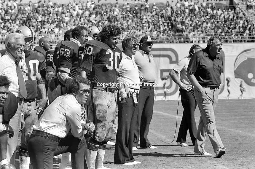 Oakland Raider sideline during game in San Diego against the Chargers. Actor James Garner (bottom left among Raiders, Van EEghen, Upshaw, Ron Wolf, & coach John Madden. (1976 photo/Ron Riesterer)