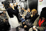 "A young woman applies makeup while another eats a hamburger on a train in Tokyo, Japan. The Japanese are well known for their civility and politeness,  but a recent governmental campaign to clamp down on lewd behavior that  may inconvenience to others -- including talking on cell phones and applying makeup while commuting on a train -- was fueled by a decline in everyday etiquette and manners. The campaign includes a series of posters seen throughout the Japan capital's extensive underground network that urges commuters to ""Do it at home."""