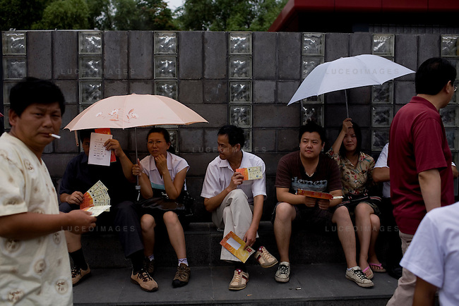 Ticket scalpers wait outside the Olympic venue trying sell tickets for upcoming events in Beijing, China on Sunday, August 17, 2008. Many prices for tickets were inflated more than 700 percent. Kevin German