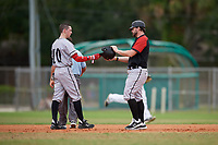 Edgewood Eagles right fielder Casey Willis (10) gives his helmet to coach Ralph Kalal in between innings during the first game of a double header against the Bethel Wildcats on March 15, 2019 at Terry Park in Fort Myers, Florida.  Bethel defeated Edgewood 6-0.  (Mike Janes/Four Seam Images)