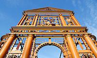 Nederland  Rotterdam 2015. De Delftsche Poort ofwel de Nieuwe Delftse Poort in Rotterdam was een stadspoort waarvan de laatste in 1764 werd gebouwd naar een ontwerp van architect Pieter de Swart. Het was reeds de derde poort op die plaats: de voorgaande twee waren wegens bouwvalligheid gesloopt. De eerste poort werd in de Middeleeuwen gebouwd en kreeg de naam de Noorderpoort en had een voorpoort. De tweede St. Joris- of Delftsche Poort werd in 1545 gebouwd. In de jaren 30 van de 20e eeuw stond de poort in de weg: Rotterdam wilde een betere doorstroming van het toenemende verkeer. Men besloot de poort zo'n honderd meter te verplaatsen. In 1939 begon men met de verplaatsing van het geheel. De onderbouw was in 1940 gereed, tijdens het bombardement werden zowel dit gedeelte als  opgeslagen beeldhouwwerken beschadigd. Een jaar later werd besloten dat  de poort niet meer afgebouwd kon worden en moest zij geheel verdwijnen. Vijftig jaar later werd er op  de oorspronkelijke plaats van de Delftsche poort aan het Pompenburg een reconstructie in staal opgericht, ontworpen door de kunstenaar Cor Kraat.