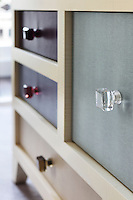 Detail of the pale blue, beige and purple leather clad drawers in the chest beside the bedroom sofa