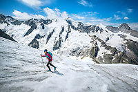 A trail runner on the Strahlegghorn crosses a small snow covered glacier, from Grindelwald, Switzerland