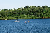 Bahia, Brazil. Canoes on a blue river estuary with mangroves on the banks.