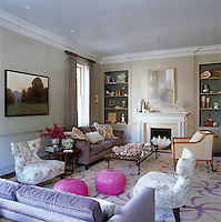 A painting by Donald Jurney is grouped with Baker chairs and John Derian pink leather pouffes in the living room