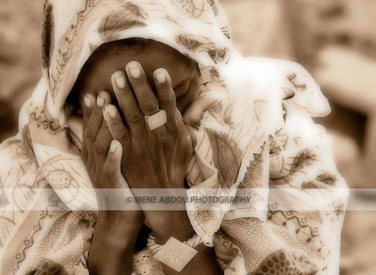 In Ouagadougou, Burkina Faso, Yuma Dicko, a young Fulani woman, covers her face in prayer.  More than half the population of this small, landlocked country is Muslim.