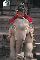 Durbar Square in Bhaktapur, Nepal, contains many temples and, scattered among them, on their steps, round their doorways and on their walls and roofs, are numerous statues. Some are large and menacing but some, as this little girl finds, are small and friendly.