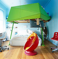 This futuristic child's bedroom combines grown-up furniture and 21st century technology in a brightly-coloured space