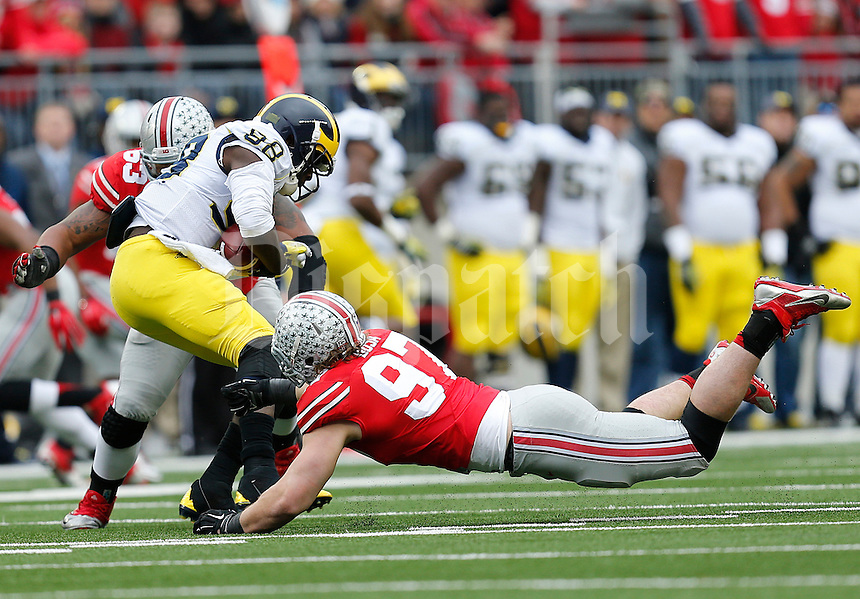 Ohio State Buckeyes defensive lineman Joey Bosa (97) and Ohio State Buckeyes defensive tackle Michael Bennett (63) sack Michigan Wolverines quarterback Devin Gardner (98) in the second quarter the college football game between the Ohio State Buckeyes and the Michigan Wolverines at Ohio Stadium in Columbus, Saturday morning, November 29, 2014. As of half time the Ohio State Buckeyes and Michigan Wolverines were tied 14 - 14. (The Columbus Dispatch / Eamon Queeney)