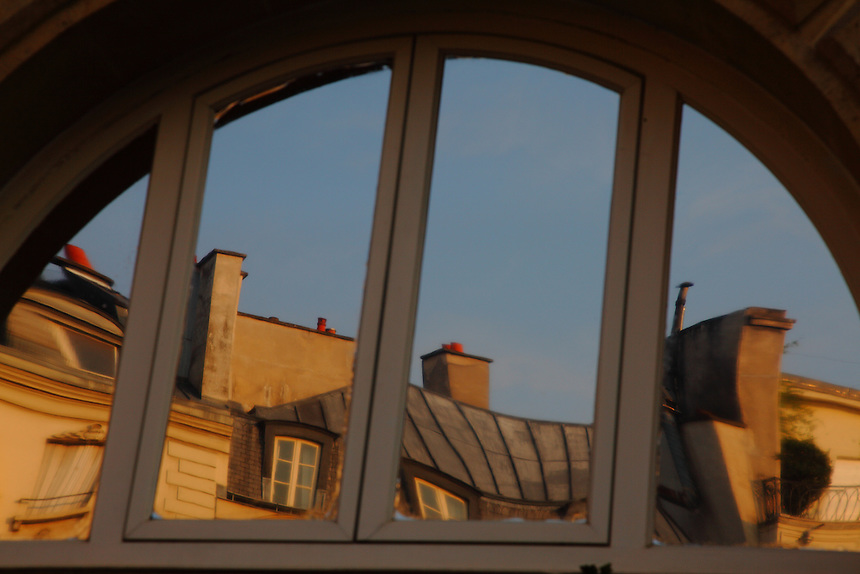 An artistic view of the typical roof of some buildings of Place Dauphine in Paris, through a reflected image on the top of a mirror window. Digitally Improved Photo.
