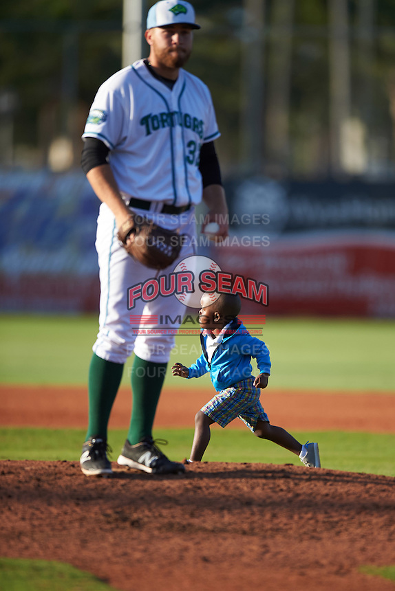 A young fan runs free on the field behind Daytona Tortugas relief pitcher Seth Varner (32) after taking a different route for the base race than planned during a game against the Fort Myers Miracle on April 17, 2016 at Jackie Robinson Ballpark in Daytona, Florida.  Fort Myers defeated Daytona 9-0.  (Mike Janes/Four Seam Images)