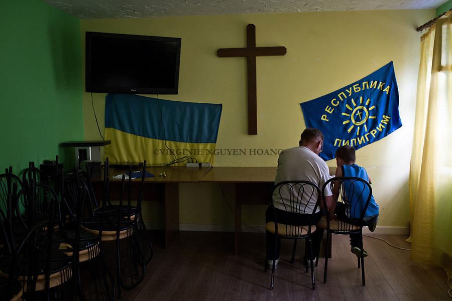 UKRAINE, Mariupol: A young boy is doing his homeworks at the foster home Piligrim with an old man volunteering in the center. <br /> <br /> UKRAINE, Mariupol: Un jeune gar&ccedil;on est en train de faire ses devoirs au foyer d'accueil Piligrim avec un vieil homme b&eacute;n&eacute;vole du centre.