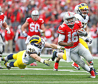 Ohio State Buckeyes quarterback J.T. Barrett (16) slips by Michigan Wolverines linebacker Ben Gedeon (42) for a late second quarter TD at Ohio Stadium on November 29, 2014. (Chris Russell/Dispatch Photo)
