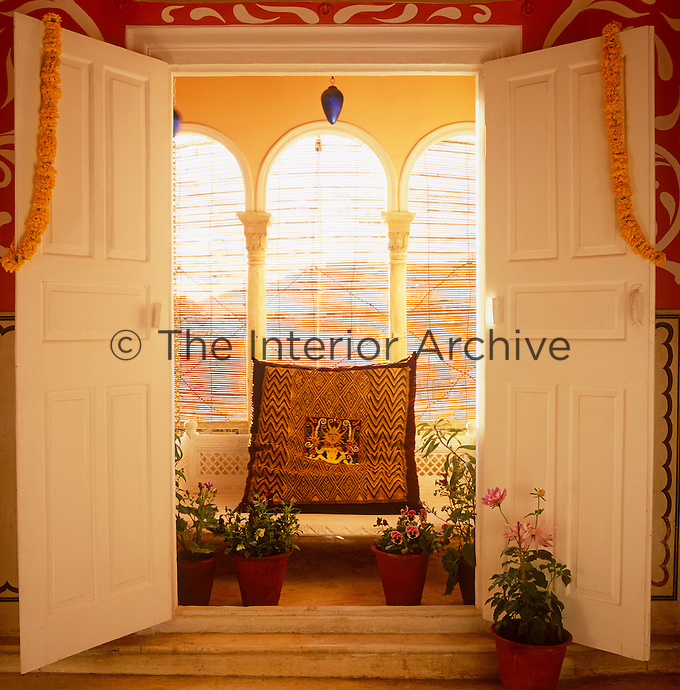A swing-chair on the balcony is seen from the open double doors of the meditation room