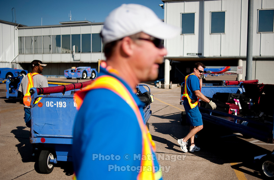 Michael Smith (cq, front) and other Southwest Airlines employees work with bags after a plane landed at Love Field Airport in Dallas, Texas, Wednesday, October 27, 2010...PHOTO/ MATT NAGER