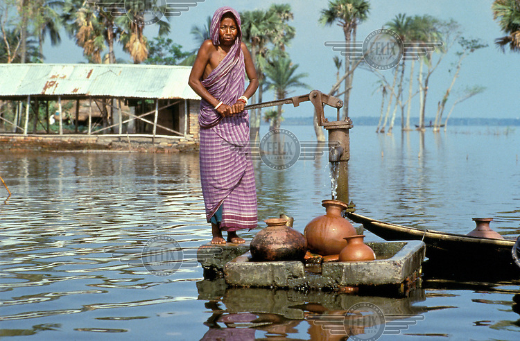 © Jim Holmes / Panos Pictures..Nr. Khulna, Bangladesh...Woman collecting water from a tube well stranded by rising flood waters on Beel Dakatia.