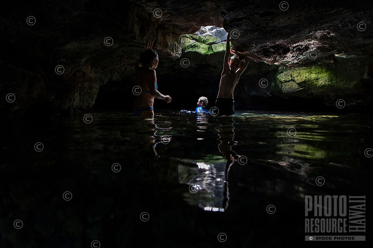 People enjoy a fresh water cave at Queen's Bath at Kiholo Bay, Big Island.