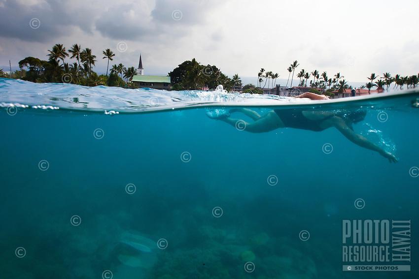 Woman swimming in Kailua-Kona bay, Big island. Photo taken above and below water