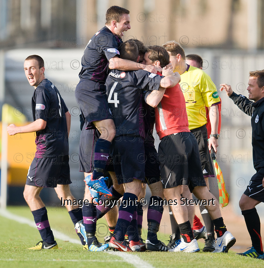 Partick's Kris Doolan (hidden) celebrates with team mates and manager Jackie McNamara after he scores Thistle's equaliser late into injury time ...