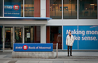 A man stands by a BMO logo in Toronto financial district April 19, 2010. The Bank of Montreal (in French, Banque de Montréal, commonly BMO in either language), or BMO Financial Group, is the fourth largest bank in Canada by deposits.