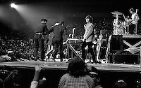 Beatles concert at the Cow Palace in San Francisco, Ca Aug 31,1965. Unidentified female is escorted off the stage as John Lennon (center) and the rest of the Beatles watch. (photo 1965/Ron Riesterer)